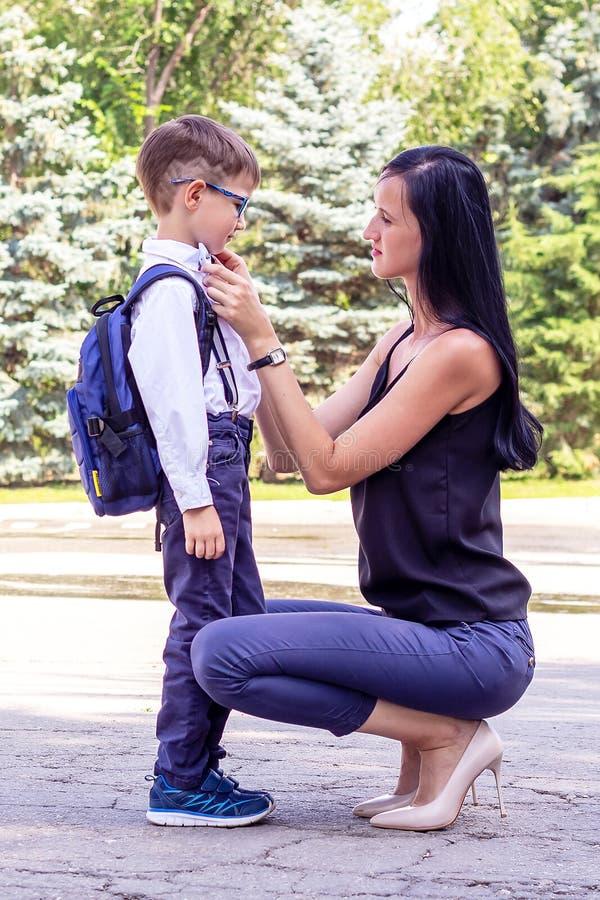 A mamã moreno nova acompanha o filho dos seus primeiro-graduadores à escola imagens de stock royalty free