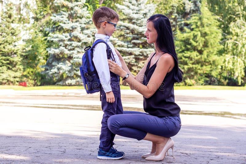 A mamã moreno nova acompanha o filho dos seus primeiro-graduadores à escola imagem de stock