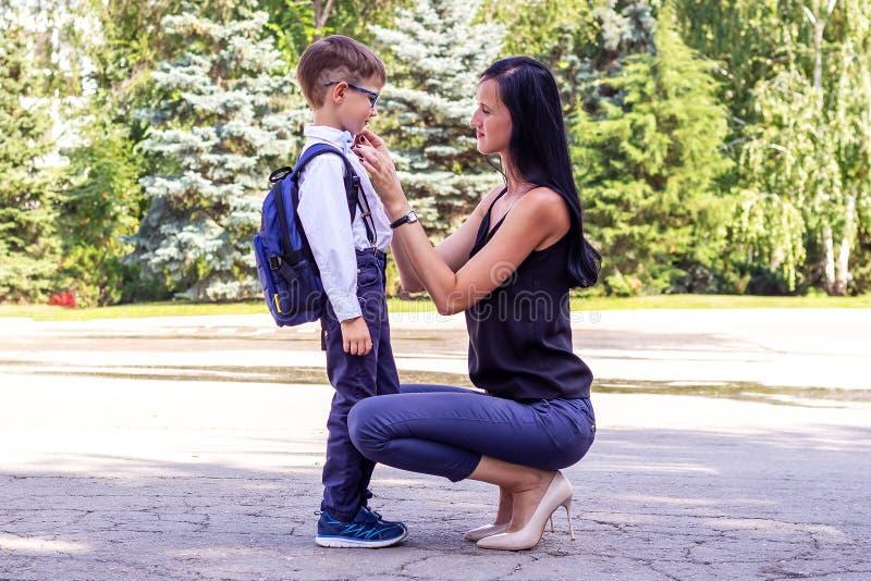 A mamã moreno nova acompanha o filho dos seus primeiro-graduadores à escola foto de stock