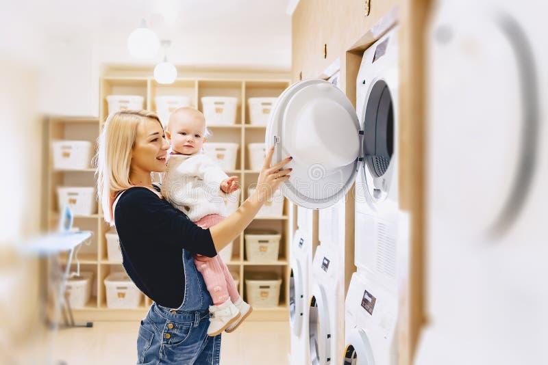 A mamã mostra a sua filha uma máquina de lavar foto de stock royalty free