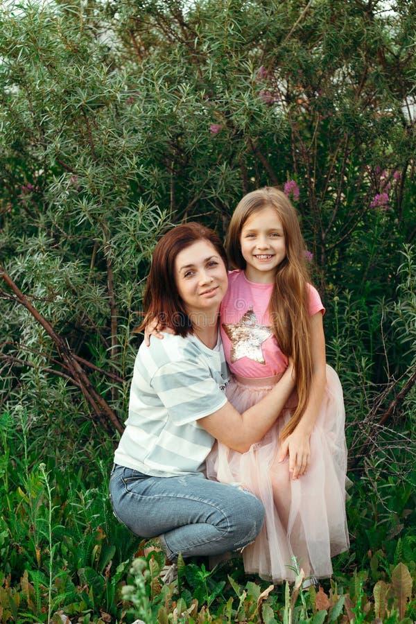 a mamã nova beija sua pouca filha no mordente contra o fundo verde em um dia de verão ensolarado imagem de stock royalty free