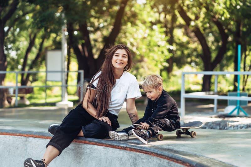 Mamã nova bonita do moderno e filho pequeno no skatepark foto de stock royalty free
