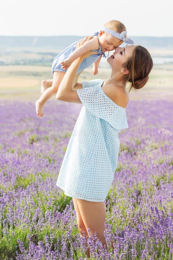 Mamã nova com a menina da criança pequena no campo da alfazema foto de stock