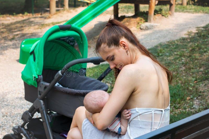 Mamã nova com sua parte externa recém-nascida, opinião de verso o bebê novo da amamentação da mãe em público, a parada ao andar c fotos de stock royalty free