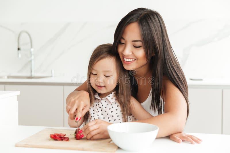 A mamã nova feliz com a filha asiática bonito pequena cortou a morango fotos de stock
