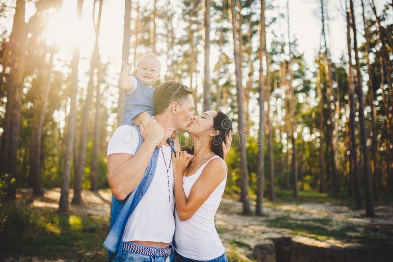 A mamã, o paizinho e a filha da família sentam-se no paizinho nos ombros, e no beijo dos pais na natureza na floresta no verão no imagens de stock