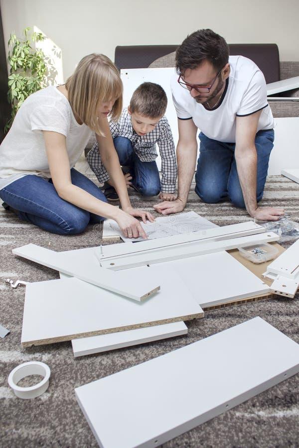 Mamã, paizinho e filho, ajoelhando-se sobre as instruções na sala de visitas no tapete Em torno deles coloque as partes de mobíli foto de stock