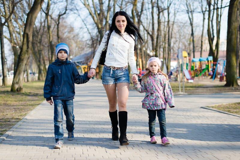 Mamã que anda no parque com câmera seu de sorriso do filho e da filha & de vista feliz na mola ou no outono imagens de stock
