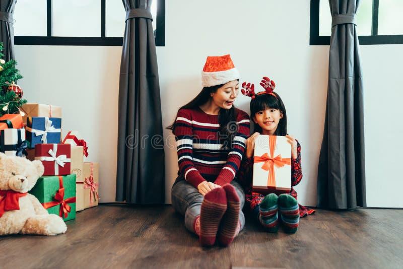Mamã que dá o presente de Natal bonito da menina imagem de stock