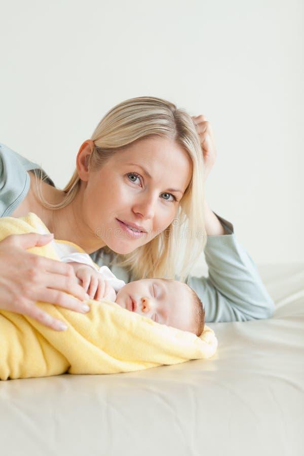 Mamã que encontra-se ao lado de seu bebê de sono fotos de stock