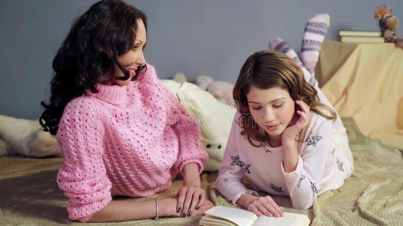 Mamã que escuta atentamente seu livro de histórias das horas de dormir da leitura da filha, família feliz foto de stock royalty free