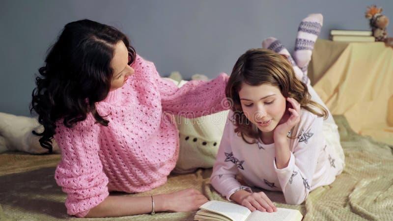 Mamã que escuta seu livro de histórias das horas de dormir da leitura da filha, afagando filha loving imagem de stock royalty free