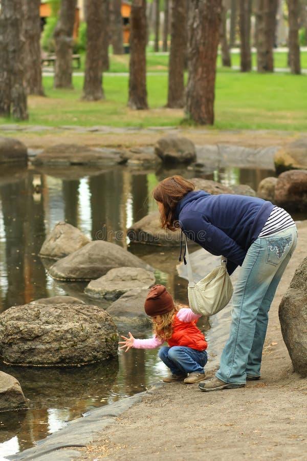 Mamã que guarda a menina da criança que verifica a lagoa do parque da água na primavera fotos de stock royalty free