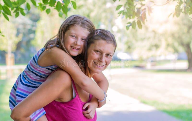 Mamã que joga com sua criança fora no parque em um dia ensolarado foto de stock