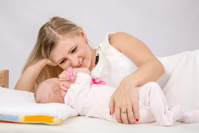 Mamã que olha lovingly seu bebê encontrar-se na cama com ele fotos de stock