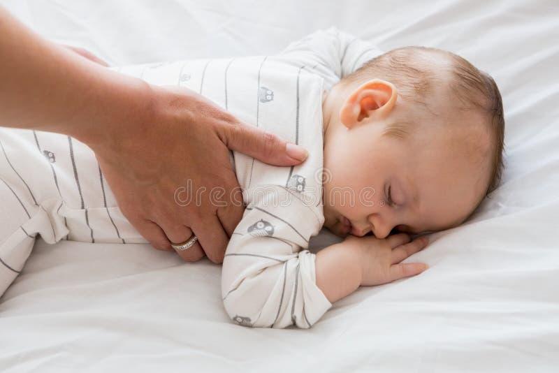 Mamã que põe o bebê para dormir na cama de bebê imagens de stock