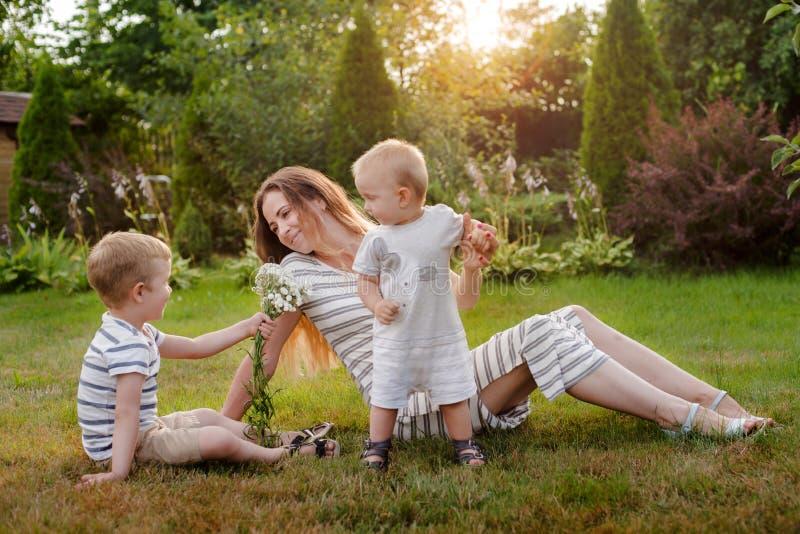 Mamã, resto de duas crianças na natureza Rivalidade de irmão Irmãos, maternidade fotos de stock