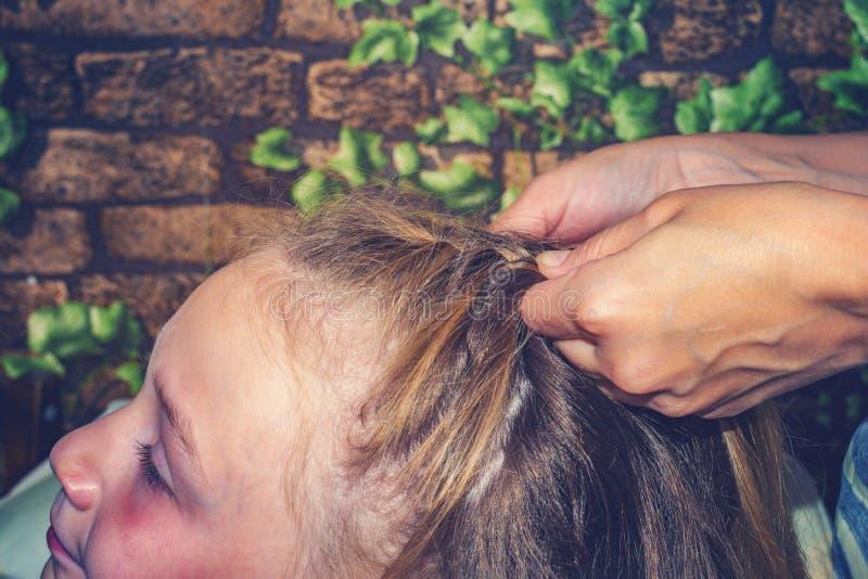 A mamã tece seu cabelo a sua filha, faz seu cabelo em casa imagem de stock royalty free