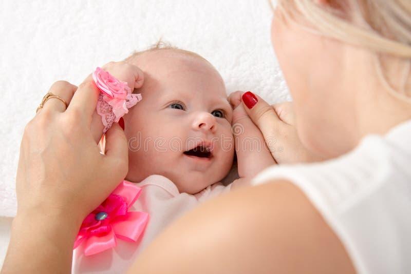 A mamã tomou os punhos do bebê e pô-los a sua cabeça fotografia de stock