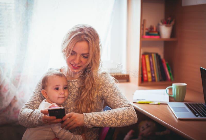 Mamã trabalhada autônomo com bebê imagem de stock royalty free