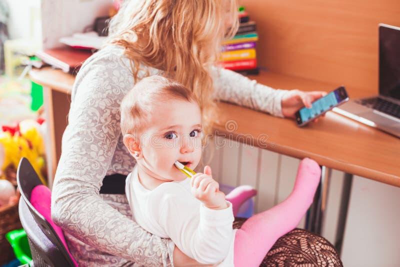 Mamã trabalhada autônomo com bebê fotografia de stock