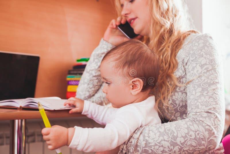 Mamã trabalhada autônomo com bebê imagem de stock