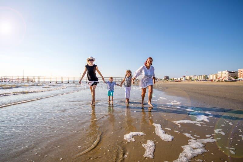 Mamãs e filho que jogam na praia foto de stock
