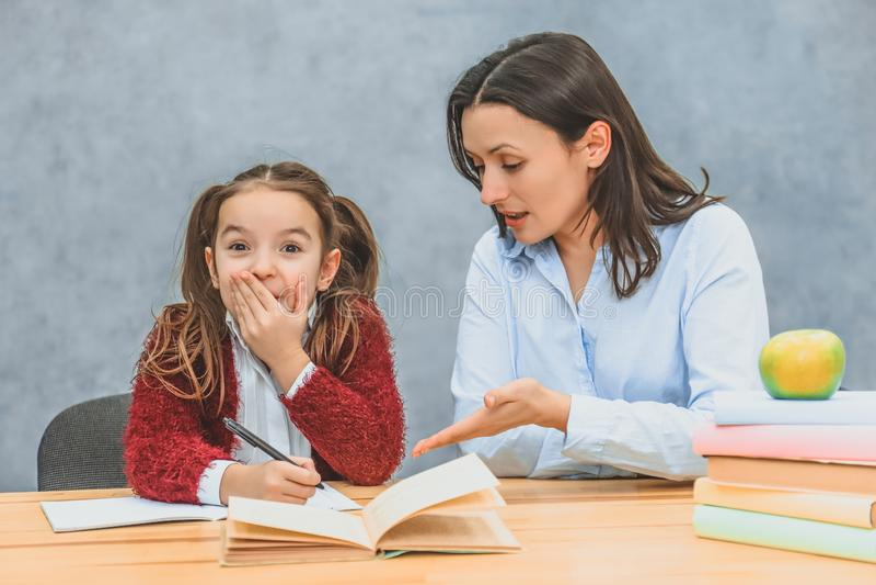 A mam? ajuda-me a fazer os trabalhos de casa da minha filha Durante isto est?o sentando-se em um fundo cinzento Uma estudante fec imagens de stock royalty free