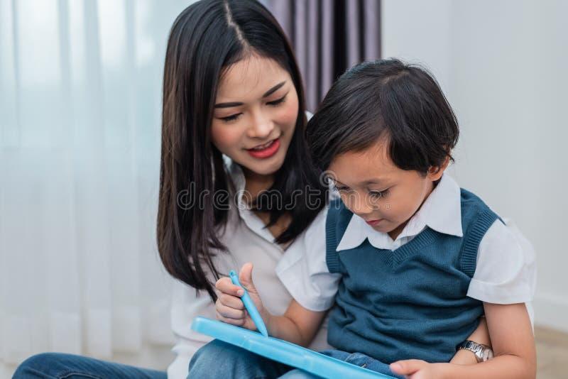 Mam? asi?tica que ense?a al muchacho lindo a unir en pizarra De nuevo a escuela y a concepto de la educaci?n Familia y hogar dulc imagen de archivo