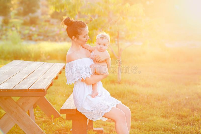 A mam? est? nutrindo sua crian?a na natureza Fam?lia feliz que senta-se no fundo do por do sol fotografia de stock royalty free