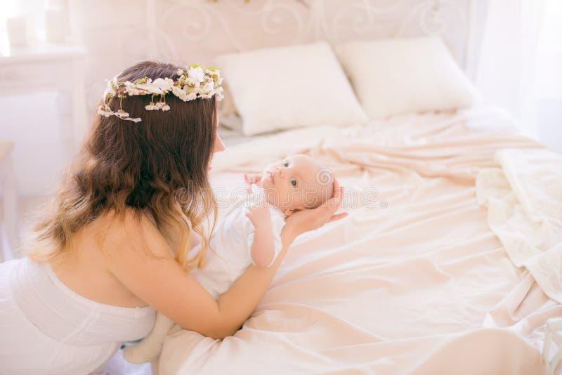 Mam? linda joven en una guirnalda de flores de cerezo en un vestido blanco que detiene a un beb? en sus brazos en un dormitorio d foto de archivo