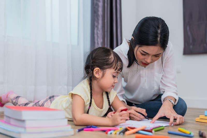 Mam? que ense?a a su hija al dibujo en clase de arte De nuevo a escuela y a concepto de la educaci?n Tema de los ni?os y de los n foto de archivo libre de regalías