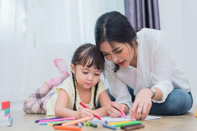 Mam? que ense?a a su hija al dibujo en clase de arte De nuevo a escuela y a concepto de la educaci?n Tema de los ni?os y de los n fotografía de archivo libre de regalías