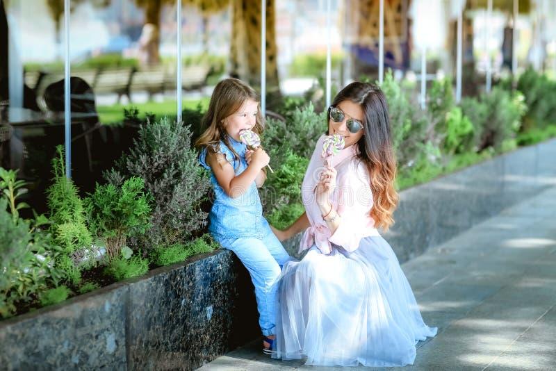 Mam? y muchacha que comen el caramelo en el parque fotografía de archivo