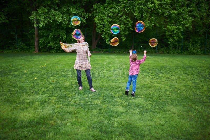 Mam? y ni?os que juegan burbujas de jab?n en el c?sped verde en el parque imagen de archivo libre de regalías