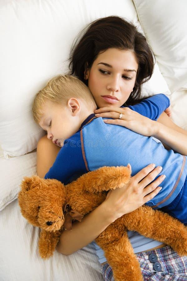 Mama con el niño durmiente. imagenes de archivo
