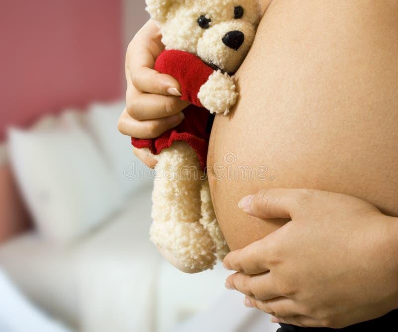 Mama con el peluche que cuenta con a un bebé imagen de archivo libre de regalías