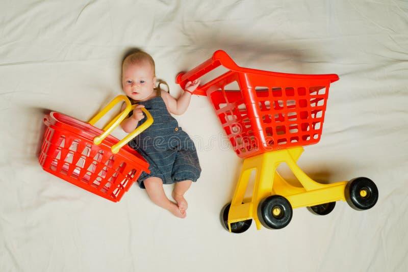 Mama de ayuda Felicidad de la niñez Oferta grande de la venta La pequeña muchacha va a hacer compras Pequeño bebé dulce Nuevos vi imagen de archivo