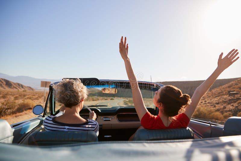 Mama, die Auto, Tochter mit den Händen in der Luft, Rückseitenansicht fährt stockbild