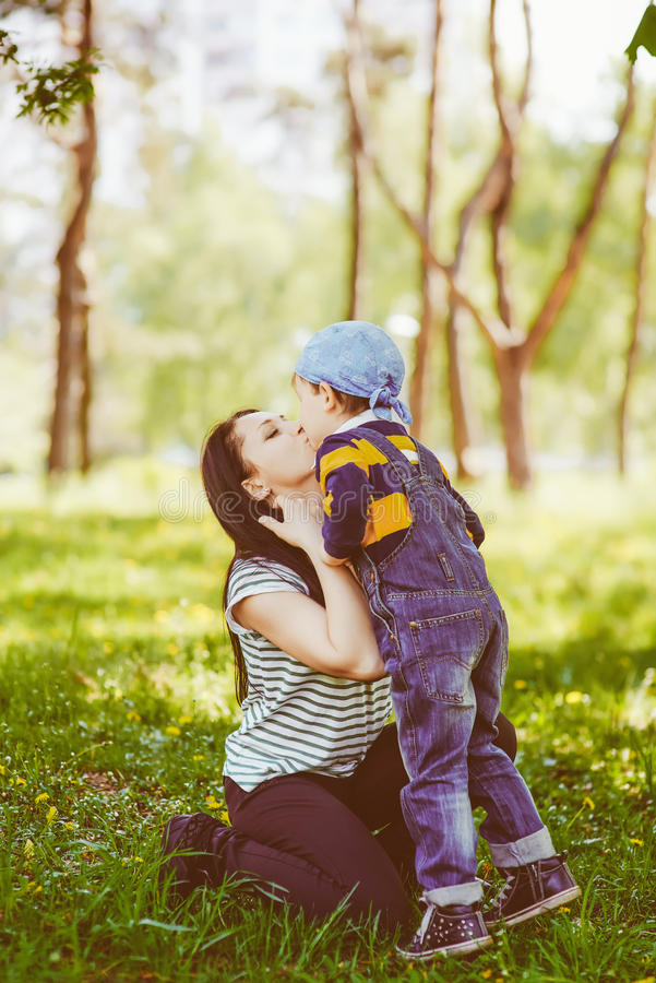 Mama die haar leuke zoon kussen stock afbeelding