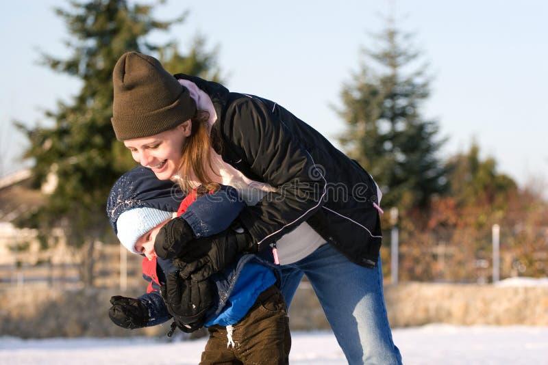 Mama e hijo que juegan en nieve imagenes de archivo