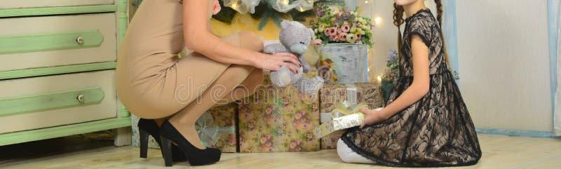 Mama i córka blisko choinki w eleganckich sukniach otwieramy prezenty, utrzymania i dekiel od prezenta, niedźwiedź zdjęcie royalty free