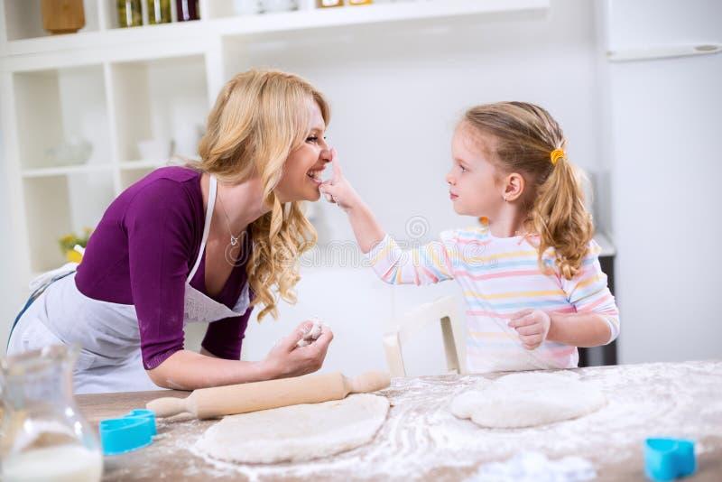 Mama i córka ma zabawę podczas gdy robią ciastu obraz royalty free