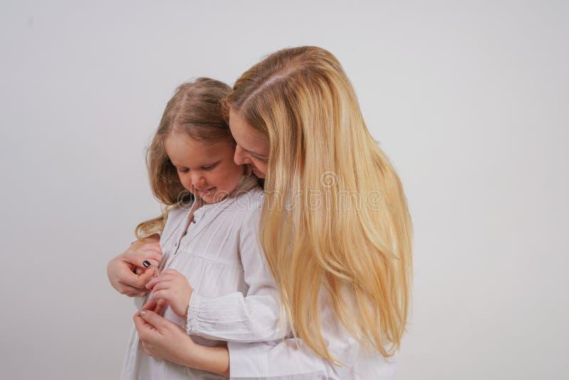 Mama i córka w białych koszula z długim blondynka włosy pozuje na stałym tle w studiu powabny rodzinny bierze opiekę e fotografia stock
