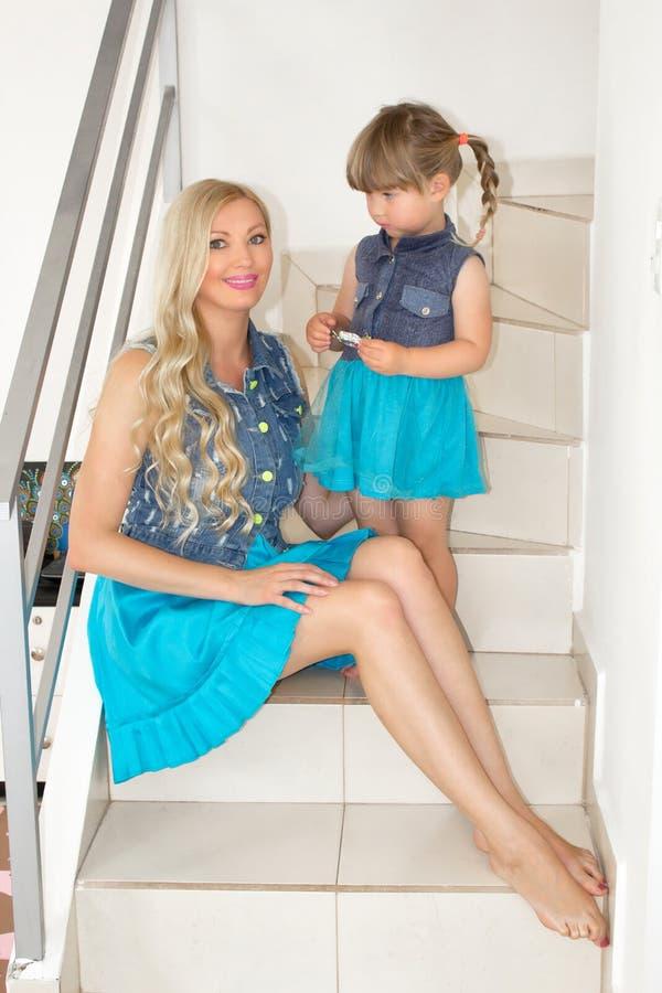 Mama i córka w identycznych sukniach siedzimy na schodkach, blondynki obraz royalty free
