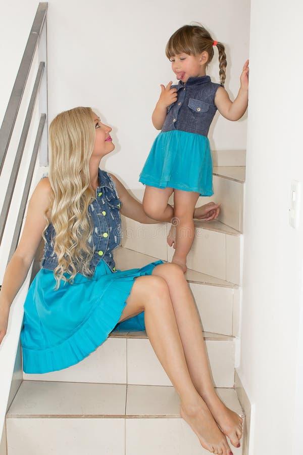 Mama i córka w identycznych sukniach siedzimy na schodkach, blondynki zdjęcie royalty free