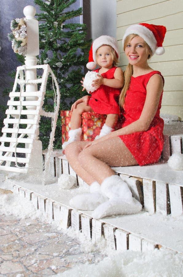 Mama i córka w Santa ` s kostiumach siedzimy pod śniegiem fotografia stock