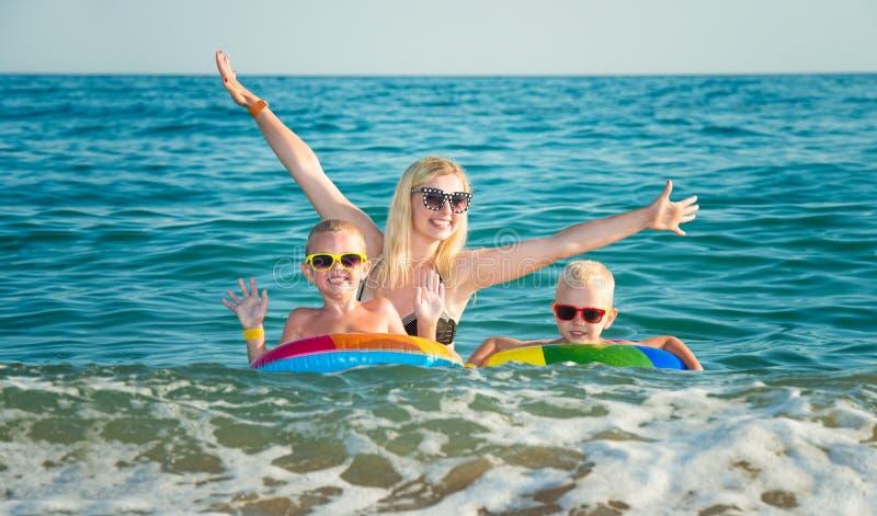 Mama i dwa syna pływamy w morzu Dzieci w jaskrawych nadmuchiwanych okręgach mój pracy widzią wakacje pracy fotografia royalty free