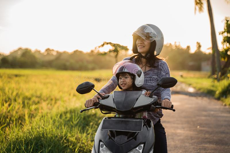 Mama i dziecko cieszymy się jeździecką motocykl hulajnogę obraz royalty free