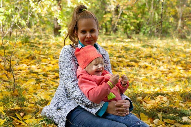 Mama i dziecko w parku na tle jesieni ulistnienie zdjęcia royalty free